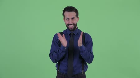 ovation : Happy young bearded Persian businessman clapping hands
