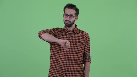 zuřivý : Angry young bearded Persian hipster man giving thumbs down