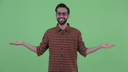 comparar : Happy young bearded Persian hipster man comparing something Stock Footage