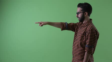 direto : Profile view of happy young bearded Persian hipster man pointing finger Stock Footage
