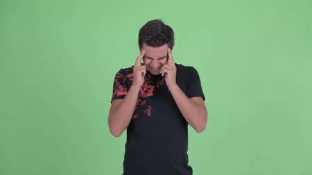 dor de cabeça : Stressed young man having headache Stock Footage