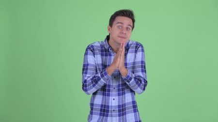 pleading : Young handsome hipster man praying Stock Footage