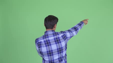 directing : Rear view of young hipster man pointing finger Stock Footage