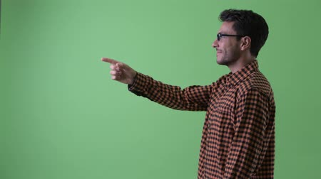 direkt : Profile view of happy young Hispanic hipster man pointing finger