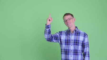 finom : Portrait of happy hipster man pointing up and giving thumbs up Stock mozgókép