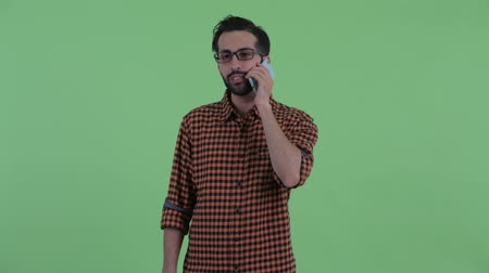 ближневосточный : Happy young bearded Persian hipster man thinking and talking on the phone Стоковые видеозаписи