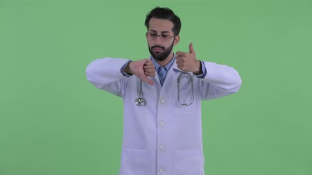 disagreement : Confused young bearded Persian man doctor choosing between thumbs up and thumbs down