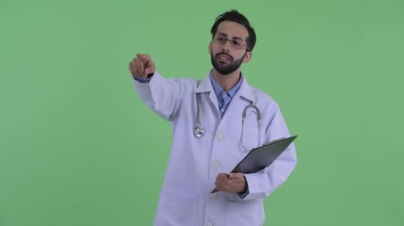 direkt : Happy young bearded Persian man doctor directing while holding clipboard