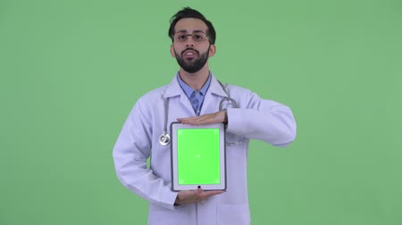 apresentador : Happy young bearded Persian man doctor talking while showing digital tablet Vídeos