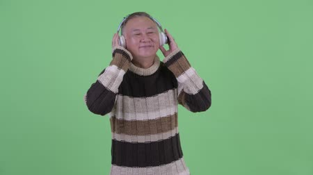grey eyes : Happy mature Japanese man listening to music