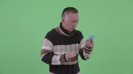 slecht nieuws : Stressed mature Japanese man using phone and getting bad news