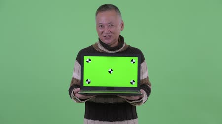 átnyújtás : Happy mature Japanese man thinking while showing laptop and talking