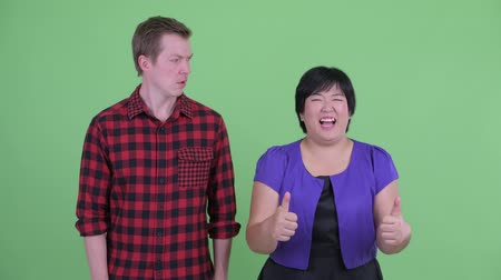 fikirler : Happy overweight Asian woman giving thumbs up with Scandinavian hipster man looking confused