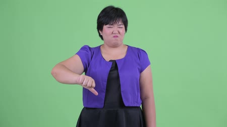 sinirlenmiş : Angry young overweight Asian woman giving thumbs down