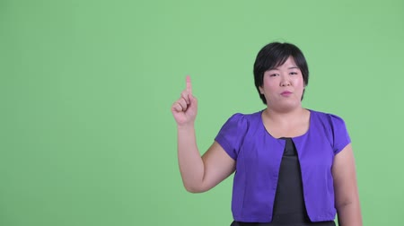 tiro : Happy young overweight Asian woman pointing up and talking