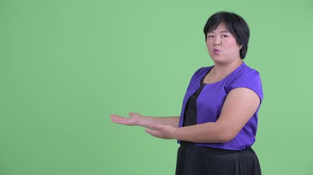 nadváha : Happy young overweight Asian woman presenting something to the back
