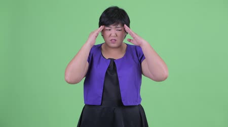 migrén : Stressed young overweight Asian woman having headache