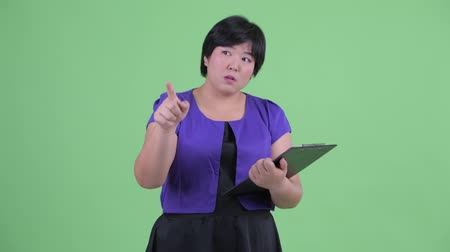 direto : Young beautiful overweight Asian woman holding clipboard and directing Stock Footage