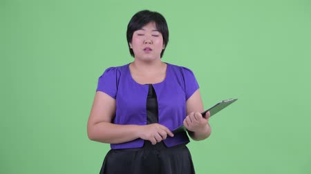 nadváha : Happy young overweight Asian woman talking while holding clipboard