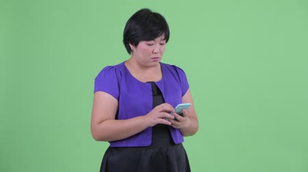 megragad : Happy young overweight Asian woman using phone and calling for taxi Stock mozgókép