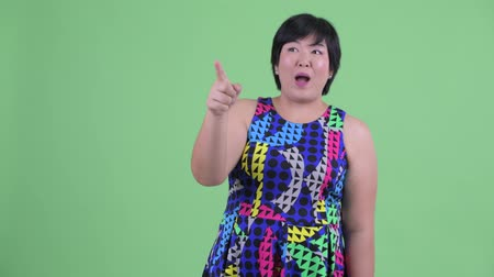 direkt : Happy young overweight Asian woman pointing finger ready to party Stok Video