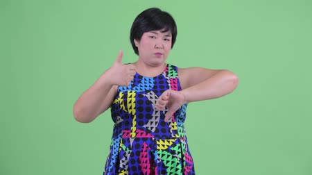 fikirler : Confused young overweight Asian woman choosing between thumbs up and thumbs down