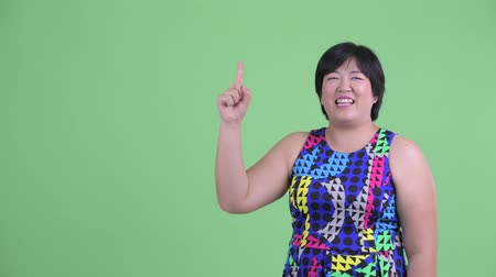 kolsuz : Happy young overweight Asian woman pointing up and looking surprised