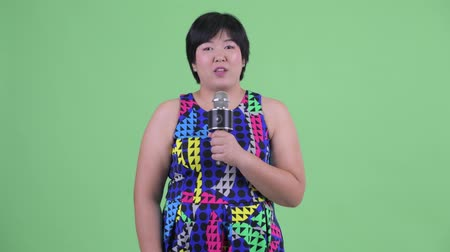 evsahibi : Happy young overweight Asian woman presenting with microphone Stok Video