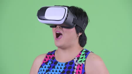 rövid : Face of happy young overweight Asian woman using virtual reality headset Stock mozgókép