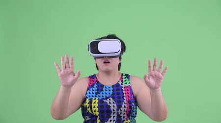 в середине : Face of happy young overweight Asian woman using virtual reality headset and looking surprised Стоковые видеозаписи