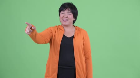 directing : Happy young overweight Asian woman pointing finger ready for gym