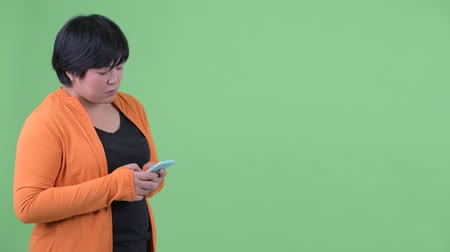 overweight : Happy young overweight Asian woman waiting while using phone ready for gym