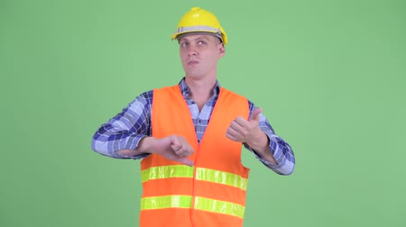 fikirler : Confused young man construction worker choosing between thumbs up and thumbs down