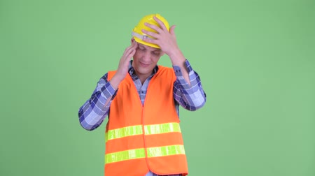 dor de cabeça : Stressed young man construction worker having headache
