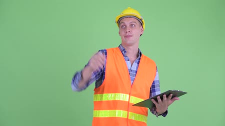 direkt : Happy young man construction worker directing while holding clipboard