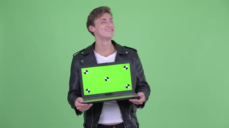 attitude : Happy young rebellious man thinking while showing laptop