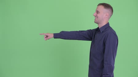 directing : Profile view of happy handsome businessman pointing finger