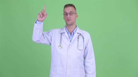 середине взрослых : Happy handsome man doctor pointing up Стоковые видеозаписи