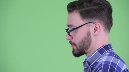 клетчатый : Closeup profile view of happy young bearded hipster man talking