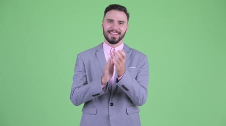 ovation : Happy young bearded businessman clapping hands