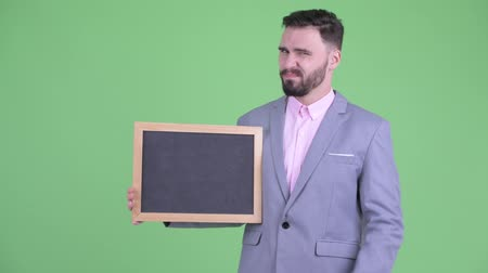ret : Stressed young bearded businessman holding blackboard and giving thumbs down Stok Video