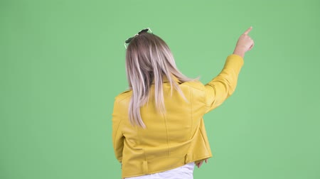 atitude : Rear view of young rebellious blonde woman pointing finger