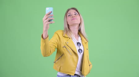 écran : Happy young rebellious blonde woman taking selfie