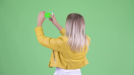 wizerunek : Rear view of young rebellious blonde woman taking picture with phone