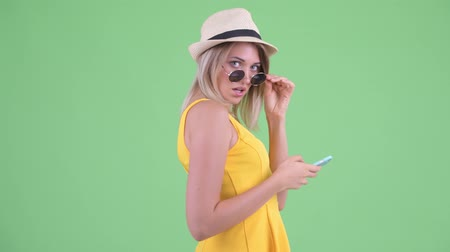 haughty : Young blonde tourist woman using phone while looking over sunglasses