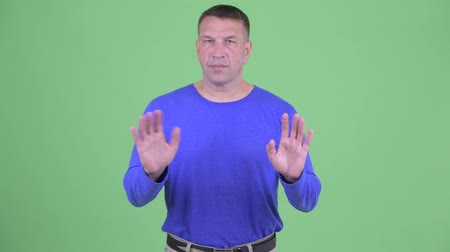 снижение : Serious macho mature man waving hand no Стоковые видеозаписи