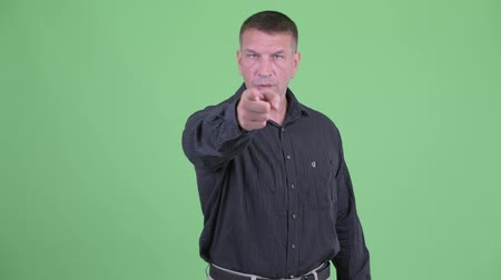 bewakingscamera : Serious macho mature businessman pointing at camera Stockvideo