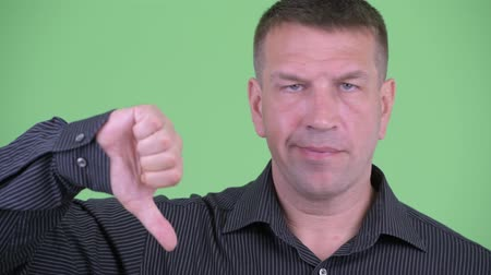 osobní strážce : Face of serious macho mature businessman giving thumbs down