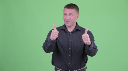 телохранитель : Happy macho mature businessman giving thumbs up and looking excited