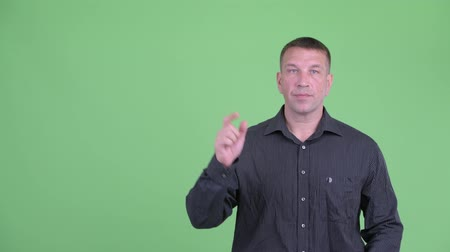 osobní strážce : Macho mature businessman pointing up and giving thumbs up Dostupné videozáznamy